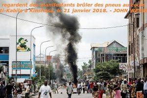 Des Kinois regardent des manifestants brûler des pneus au cours d'une marche anti-Kabila à Kinshasa, le 21 janvier 2018. - JOHN WESSELS [AFP]