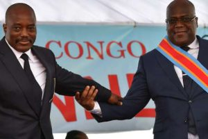 Democratic Republic of the Congo's newly inaugurated President Felix Tshisekedi (R) walks off the podium with outgoing President Joseph Kabila after he was officially handed over the instruments of power during his inauguration ceremony at the Presidency in Kinshasa on January 24, 2019. - Opposition leader Felix Tshisekedi was sworn in on January 24 as president of Democratic Republic of Congo, marking the country's first-ever peaceful handover of power after chaotic and bitterly-disputed elections. (Photo by TONY KARUMBA / AFP)