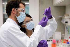 Le chimiste Samuel Raccio teste le dispositif mis au point par Hemolytics avec l'une des collaboratrices de l'équipe de chercheurs. — © Nicolas Brodard pour Le Temps